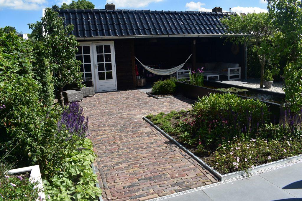 landelijke tuin met oud gebakken waaltjes, Douglas kapschuur een vijver en wit grind