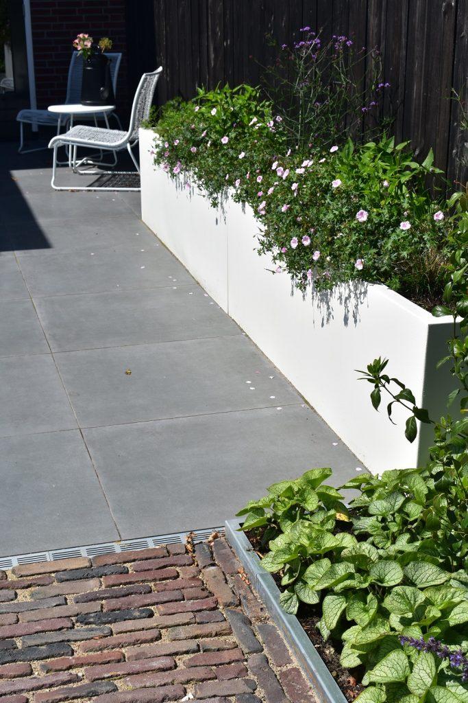 Landelijke tuin met witte bloembakken, GeoCeramica en oud gebakken waalformaat