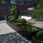 Landelijke tuin met wit grind, oud gebakken waaltjes, zwarte verticale schutting en witte bloembakken
