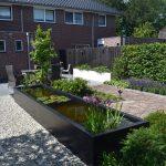 Landelijke tuin met antraciete vijver, wit grind , witte bloembakken en oud gebakken waaltjes