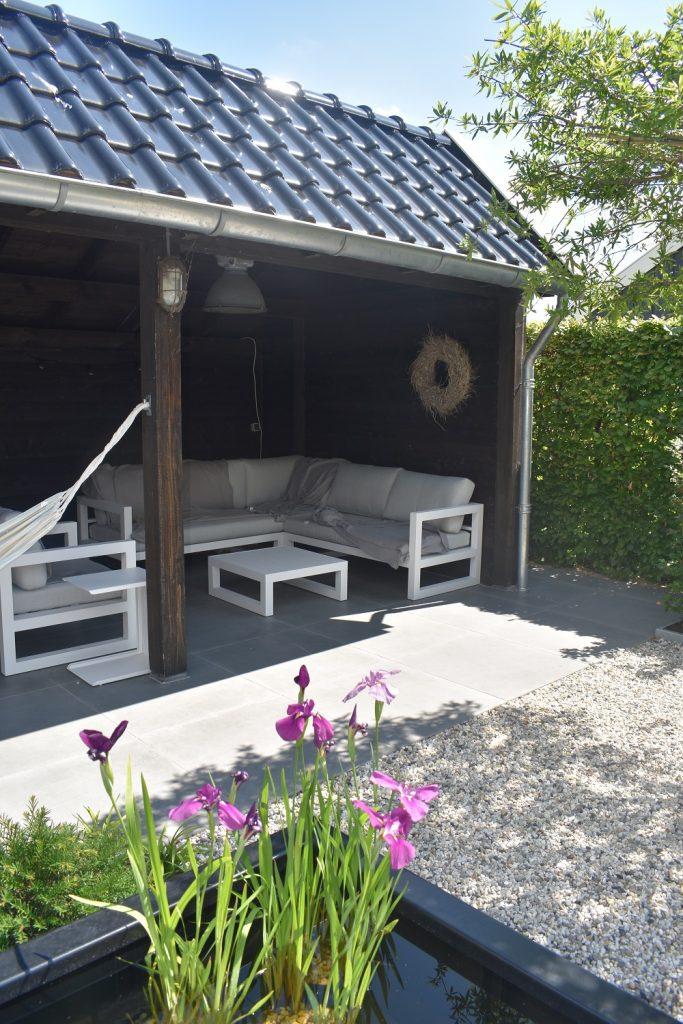 Landelijke tuin met keramische tegels in grijs, Douglas kapschuur en wit grind
