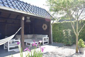 Landelijke tuin met Douglas kapschuur antraciet, wit grind, keramische tegels en dakplataan