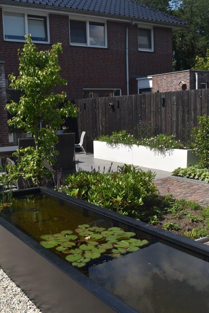 Landelijke tuin met zwarte schutting, witte bloembakken en vijver