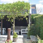 Landelijke tuin met wit grind, plantaan en Douglas kapschuur in oud antraciet