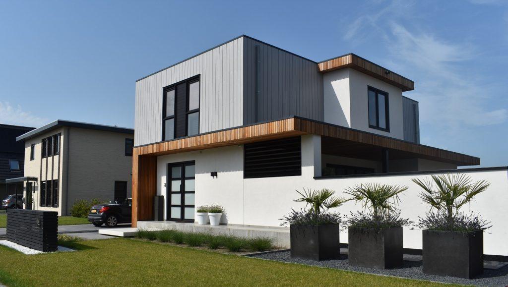 Voorkant woning met zwarte bakken en schellevis kantopsluiting grijs